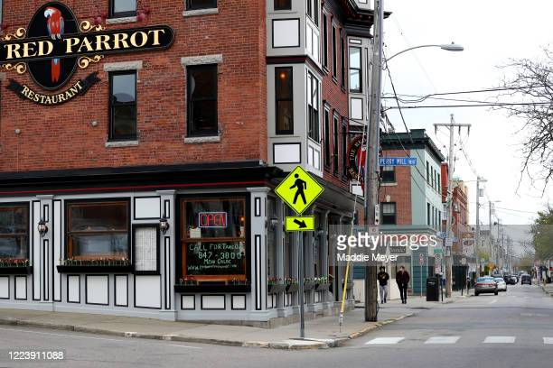 Pedestrians walk down Thames Street on May 09, 2020 in Newport, Rhode Island. Non-critical retail establishments began opening their doors with...
