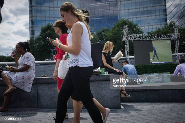 Pedestrians walk in a bridge as a woman reads a book in London 26 July 2018 According to the Met Office July is likely to be the hottest month since...