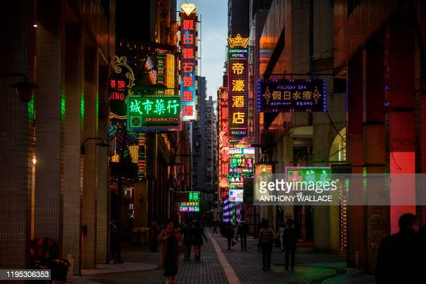 Pedestrians walk in an alleyway lined with neon signs in Macau on January 22 after the former Portuguese colony reported its first case of the new...