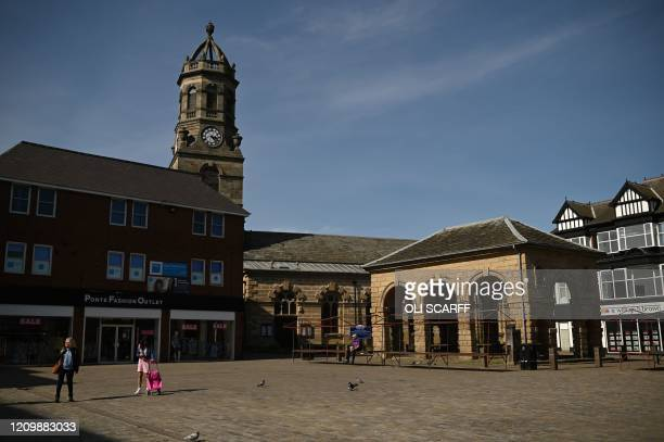 Pedestrians walk in an otherwise empty town centre in Pontefract northern England on April 14 as life in Britain continues during the nationwide...