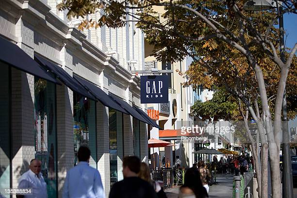 Pedestrians walk in front of a Gap Inc Kids store at the Third Street Promenade outdoor mall in Santa Monica California US on Monday Dec 5 2011 Since...