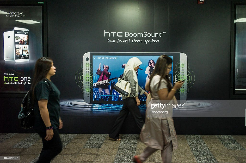 Pedestrians walk in front of a HTC Corp. advertisement in Kuala Lumpur, Malaysia, on Thursday, April 25, 2013. Malaysians will go to the polls on May 5. Prime Minister Najib Razak's National Front coalition is seeking to extend its 55 years of unbroken rule in the face of a resurgent opposition led by Anwar Ibrahim. Photographer: Sanjit Das/Bloomberg via Getty Images