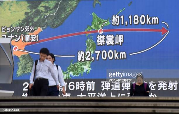 TOPSHOT Pedestrians walk in front of a huge screen displaying a map of Japan and the Korean Peninsula in Tokyo on August 29 following a North Korean...