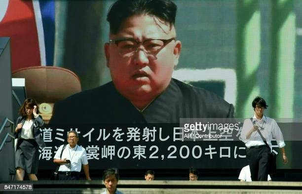 TOPSHOT Pedestrians walk in front of a large video screen in Tokyo broadcasting a news report showing North Korean leader Kim JongUn following a...