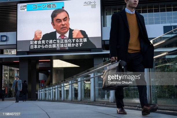 Pedestrians walk in front of a monitor displaying a news broadcast on former Nissan Motor Co Chairman Carlos Ghosn on January 09 2020 in Tokyo Japan...