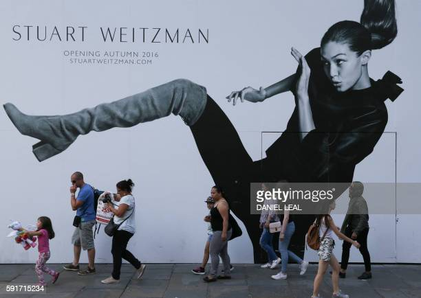 Pedestrians walk in front of a placard advertising a soon-to-open shop in Regent street, central London on August 17, 2016 Retail sales in Britain, a...