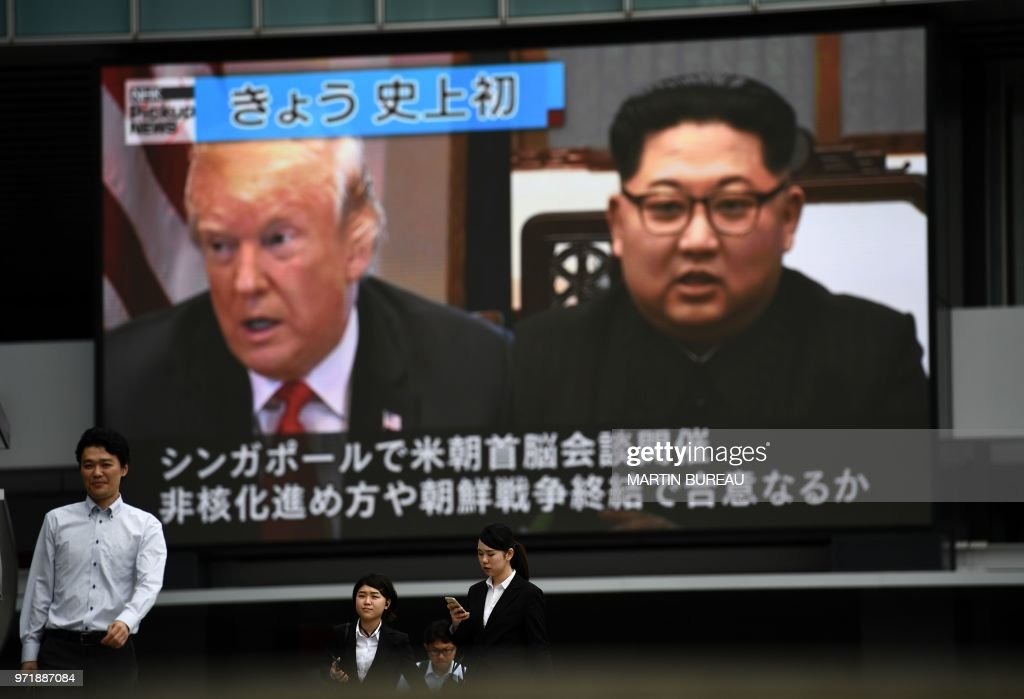 TOPSHOT - Pedestrians walk in front of a screen showing a news report displaying portraits of US President Donald Trump and North Korean leader Kim Jong Un, in Tokyo on June 12, 2018. - Trump and Kim have become on June 12 the first sitting US and North Korean leaders to meet, shake hands and negotiate to end a decades-old nuclear stand-off.