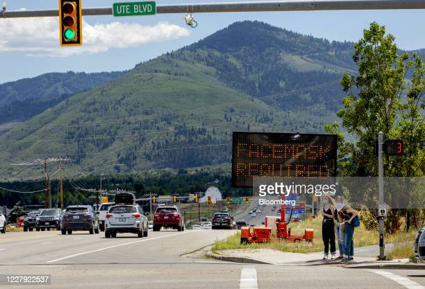"""Pedestrians walk in front of a street sign that reads """"Face Mask Requried"""" in Summit County near Park City, Utah, U.S., on Saturday, Aug. 1, 2020...."""