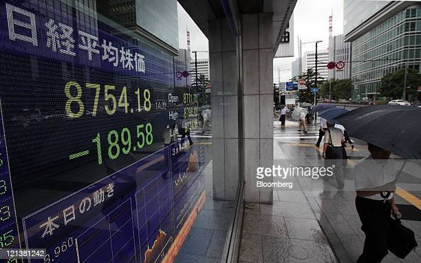 Pedestrians walk in front of an electronic stock board displaying a midday figure of the Nikkei 225 Stock Average outside a securities firm in Tokyo,...