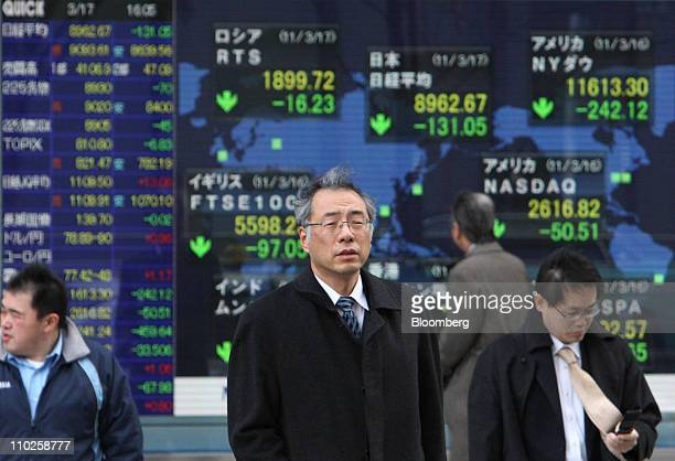 Pedestrians walk in front of an electronic stock board outside a securities firm in Tokyo Japan on Thursday March 17 2011 Japanese equities reversed...