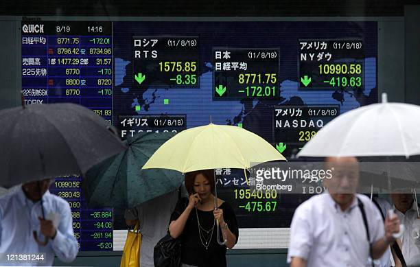 Pedestrians walk in front of an electronic stock board outside a securities firm in Tokyo, Japan, on Friday, Aug. 19, 2011. Japanese stocks fell for...