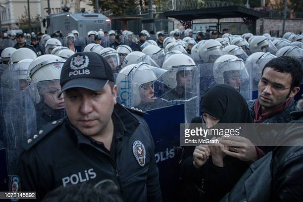 Pedestrians walk in front of female riot police as they block protesters from marching down Istiklal street during a demonstration marking...