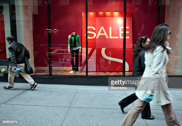 Pedestrians walk in front of large sale signs in the front windows of Ann Taylor Loft in New York US on Monday Dec 29 2008 US retailers face a wave...