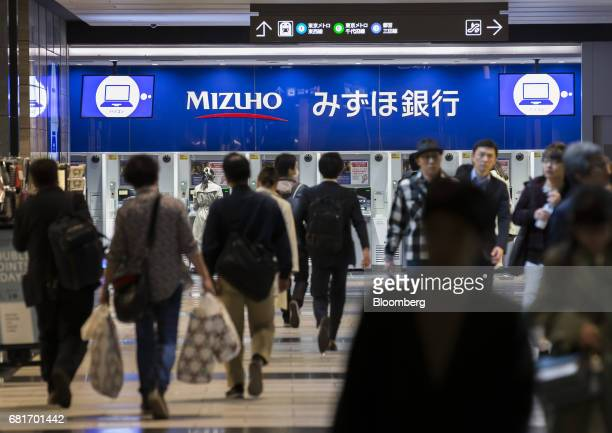 Pedestrians walk in front of Mizuho Bank Ltd automated teller machines outside the Mizuho Financial Group Inc headquarters building in Tokyo Japan on...