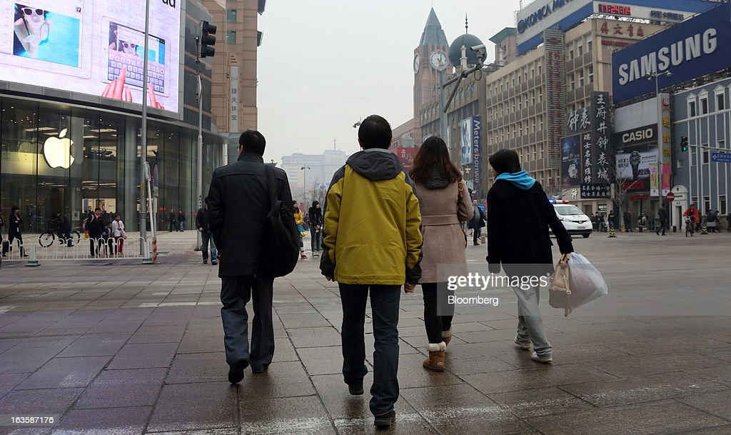 Pedestrians walk in front of the Apple Inc. store, left, and a Samsung Electronics Co. advertisement in the Wangfujing area of Beijing, China, on Tuesday, March 12, 2013. Apple's Wangfujing store is the largest in Asia. Photographer: Tomohiro Ohsumi/Bloomberg via Getty Images