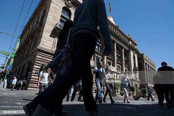Pedestrians walk in front of the Banco de Mexico building in Mexico City Mexico on Wednesday Feb 27 2013 The central bank's fivemember board is...