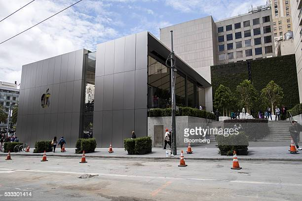 Pedestrians walk in front of the new Apple Inc flagship store at Union Square during the grand opening in San Francisco California US on Saturday May...