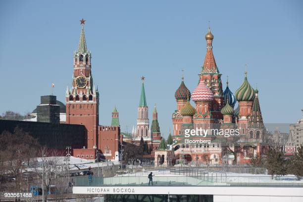 Pedestrians walk in front of the Spasskaya tower of the Kremlin left and St Basil's cathedral during presidential elections in Moscow Russia on...