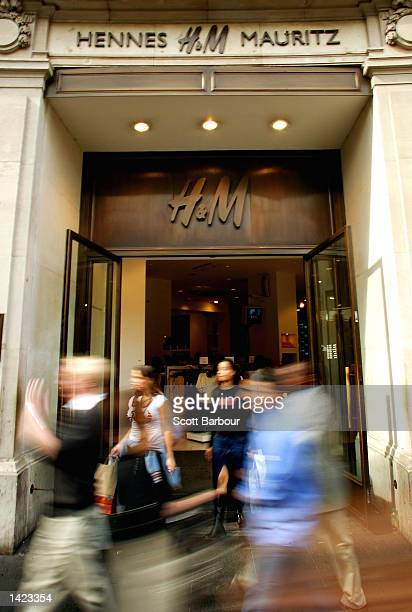 Pedestrians walk in front of the Swedish fashion group store Hennes & Mauritz on Oxford Street September 20, 2002 in London, England. Hennes &...