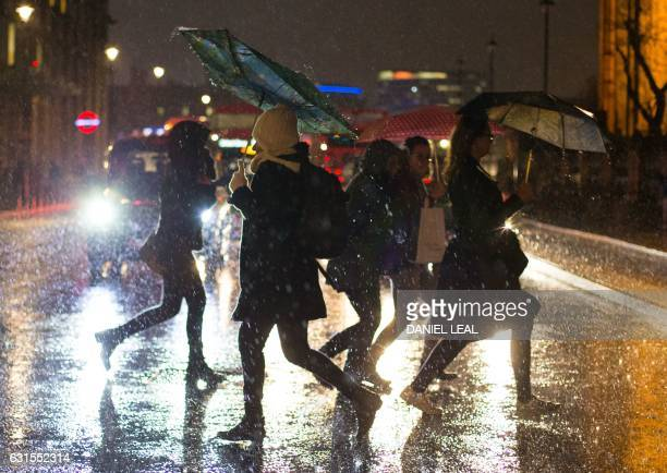 TOPSHOT Pedestrians walk in heavy rain near the Houses of Parliament in central London on January 12 2017 Britain's Met Office weather centre issued...