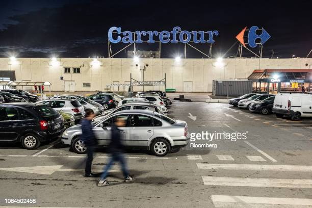 Pedestrians walk in the parking lot outside a Carrefour SA hypermarket store at night in Marseille France on Thursday Jan 17 2019Shares in French...