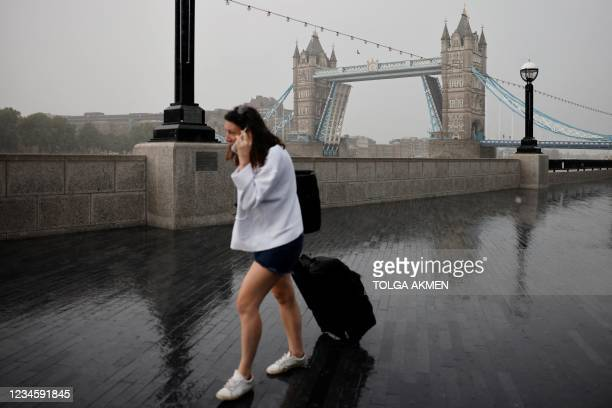 Pedestrians walk in the rain by the river Thames as Tower Bridge is stuck in an open position due to a technical fault, in central London on August...