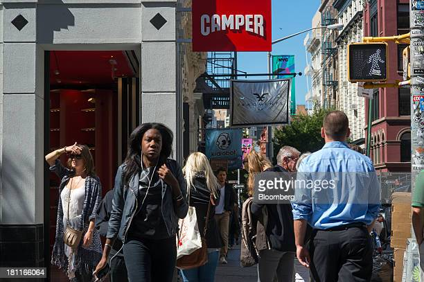 Pedestrians walk in the shopping district of Soho in New York US on Wednesday Sept 18 2013 Consumers views of the US economic outlook deteriorated in...