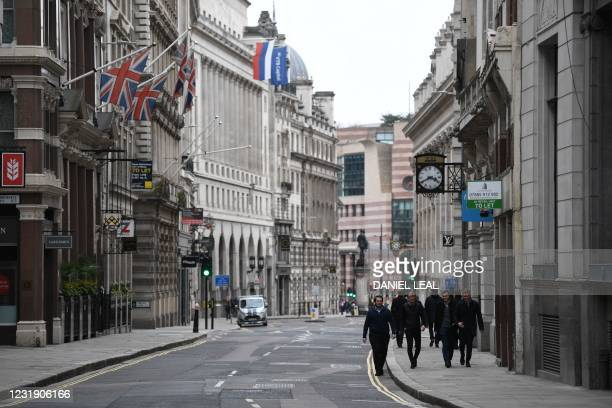 Pedestrians walk in the street in the City of London on March 24, 2021 as life continues with England following a government roadmap to easing the...