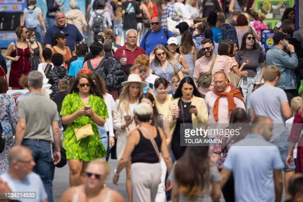 Pedestrians walk in the summer sunshine in central London on July 26, 2021. - For the first time in the latest wave of coronavirus covid-19...