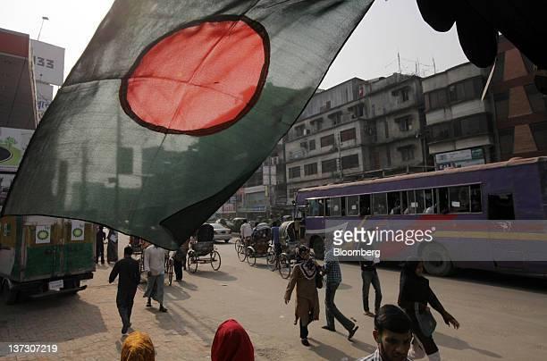 Pedestrians walk near a Bangladeshi national flag in Dhaka Bangladesh on Sunday Jan 8 2012 Bangladesh's central bank this month raised interest rates...