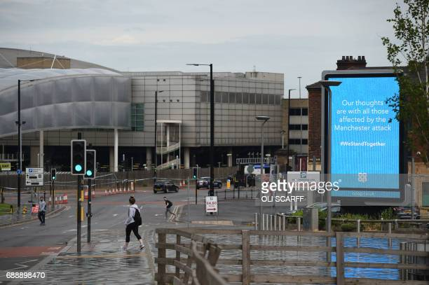 Pedestrians walk near a LED billboard with a message of support to those affected by the Manchester attack outside Victoria Station in Manchester on...