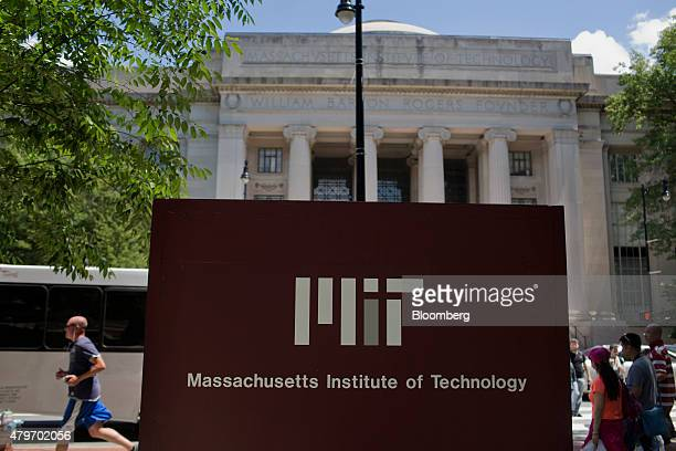 Pedestrians walk near a sign in front of the William Barton Rogers Building at the Massachusetts Institute of Technology campus in Cambridge...