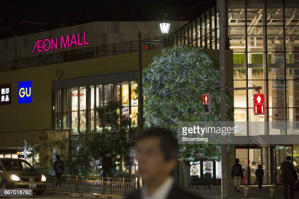 Pedestrians walk near an Aeon shopping mall operated by Aeon Mall Co a unit of Aeon Co in Tokyo Japan on Monday April 10 2017 Aeon Co Japan's biggest...
