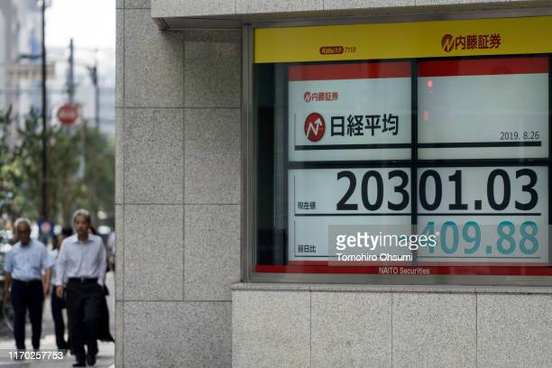 Pedestrians walk near an electronic stock board displaying the Nikkei 225 Stock Average figure on August 26, 2019 in Tokyo, Japan. Japanese stocks...