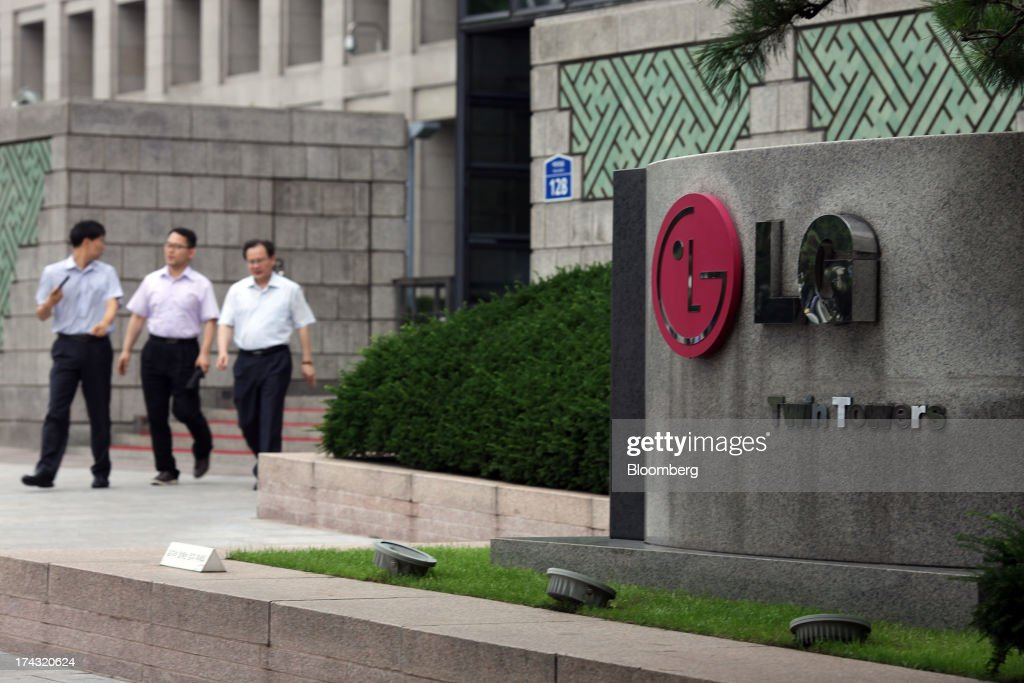 Pedestrians walk near signage for the LG Twin Towers, which houses LG Corp. subsidiaries including LG Electronics Inc., LG Display Co., LG Chem Ltd. and LG Household & Health Care Ltd., in Seoul, South Korea, on Wednesday, July 24, 2013. LG Electronics, the worlds second-largest television maker, posted second-quarter profit that missed analyst estimates on slowing demand for sets and increased spending on marketing for smartphones. Photographer: Woohae Cho/Bloomberg via Getty Images
