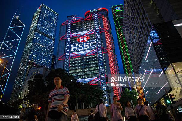 Pedestrians walk near the Bank of China Tower from left Cheung Kong Center Bank of China Building HSBC Holdings Plc headquarters Standard Chartered...