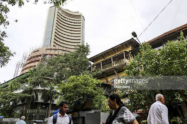 Pedestrians walk near the Bombay Stock Exchange left in Mumbai India on Monday June 27 2016 Most Indian stocks advanced led by companies tied to the...