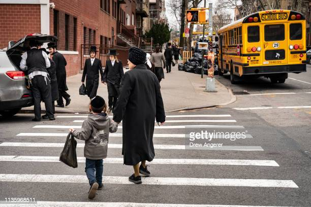 Pedestrians walk near the Yeshiva Kehilath Yakov School in the South Williamsburg neighborhood April 9 2019 in the Brooklyn borough of New York City...