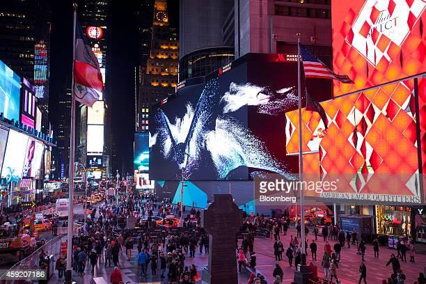 Pedestrians walk near Vornado Realty Trust's 330foot digital billboard center wrapped around the front of the Marriott Marquis Hotel on Broadway...