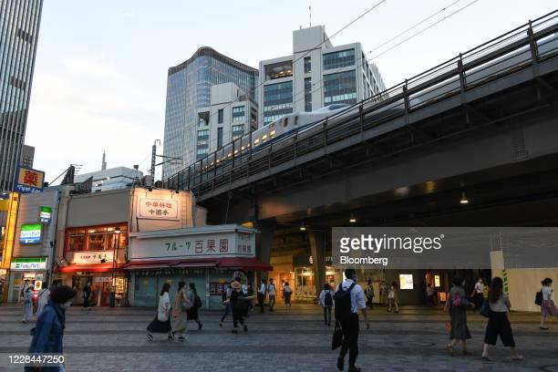 Pedestrians walk near Yurakucho station as a Shinkansen bullet train travels along a track track in Tokyo, Japan, on Thursday, Sept. 3, 2020. In...
