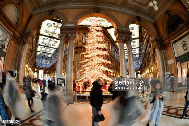 Pedestrians walk next to a Christmas tree at Galleria Alberto Sordi in Rome on December 28 2017 / AFP PHOTO / Andreas SOLARO