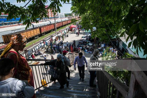 Pedestrians walk on a flight of staircase as customers browse stalls at a market near Dushanbe Station in Dushanbe Tajikistan on Sunday April 22 2018...