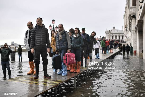 Pedestrians walk on a footbridge across the flooded Riva degli Schiavoni embankment after an exceptional overnight Alta Acqua high tide water level...