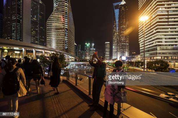 Pedestrians walk on a footbridge as commercial buildings stand illuminated at night in the Lujiazui Financial District in Shanghai China on Friday...