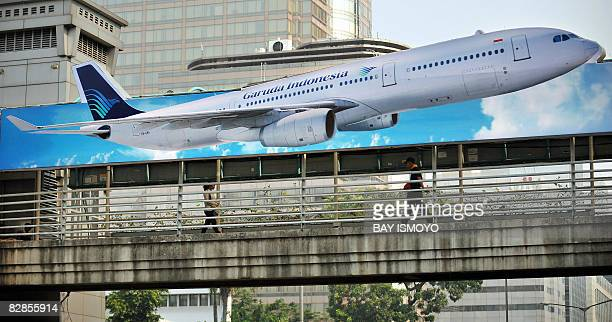 Pedestrians walk on a foot-over-bridge decorated with an advertisement of Garuda Indonesia Airlines in Jakarta on September 16, 2008. Garuda is the...