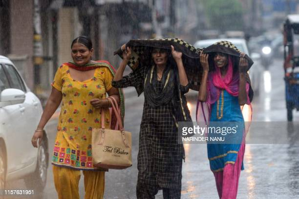 Pedestrians walk on a road during heavy rainfalls in Amritsar on July 25, 2019.