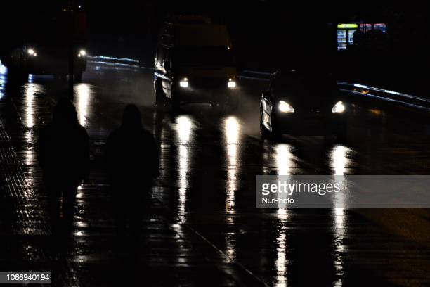 Pedestrians walk on a sidewalk next to a raindrenched road illuminated by the headlights of cars during a heavy rainfall in Ankara Turkey on November...