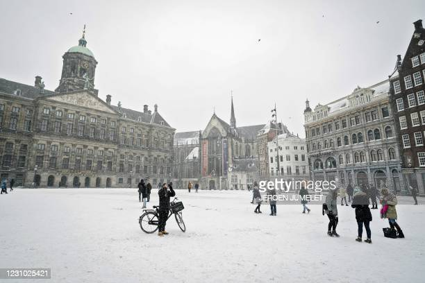 Pedestrians walk on a snow covered Dam Square in Amsterdam, on February 7, 2021. / Netherlands OUT