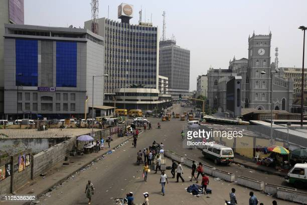 Pedestrians walk on a street in the business district in Lagos Nigeria on Saturday Feb 16 2019 A lastminute delay of Nigerias general elections by a...