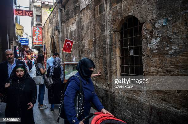 Pedestrians walk on a street near a streetvendor in Gaziantep in the southwest province of Turkey on May 1 2018 In the Turkish city of Gaziantep home...